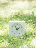 White simple clock on lawn yard, 1:55 one fifty five Stock Image
