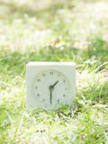 White simple clock on lawn yard, 1:30 one thirty half Royalty Free Stock Image