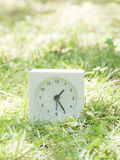 White simple clock on lawn yard, 1:25 one twenty five Royalty Free Stock Images