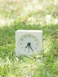 White simple clock on lawn yard, 7:25 seven twenty five. White rectangle simple clock on lawn yard, 7:25 seven twenty five Stock Photo