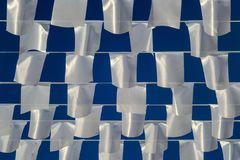 White rectangular flags hanging on ropes on background of blue sky Stock Image