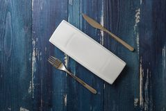 White rectangular Plate with fork and knife on blue wooden backg Stock Photos
