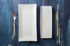 White rectangular Plates with fork and knife on blue wooden back Stock Image