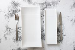 White rectangular Plates with fork and knife on white wooden bac Stock Photography