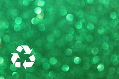 White recycle sign and green glitter lights background. defocused lights. Stock Photos