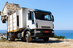 White recycling truck stays near Paleochora town on Crete island, Greece Royalty Free Stock Photos