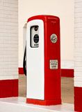 White and red ancient gas pump. Ancient gas pump painted in bright white and red in the setting of an old gas station royalty free stock photos