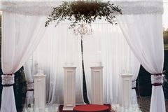 White and red arch and aisle at wedding reception in park, with. Red bouquet stock image