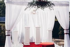 White and red arch and aisle at wedding reception in park. Wedding ceremony royalty free stock image