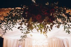 White and red arch and aisle at wedding reception in park, with. Red bouquet et evening ceremony in light stock images