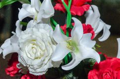 White and red artificial flowers lilies and roses on a black background Royalty Free Stock Images