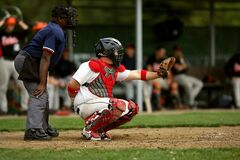 White and Red Baseball Player With Black Face Helmet and Brown Leather Mitts Royalty Free Stock Photo