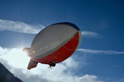 White and Red Blimp Flying Royalty Free Stock Image