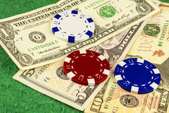 White, red and blue chips lie on bills one, five and ten dollars. On the green cloth of the poker table is one, five and ten dollar bills and white, blue and red Royalty Free Stock Photos