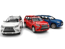 White, red and blue modern SUVs - parked side by side Stock Image