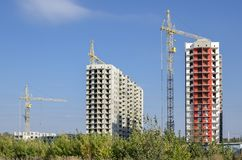 White and red buildings against the blue sky. Side view of two multicolored high-rise buildings under construction with tower cranes Stock Photos