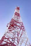 White-red cell tower or mobile tower on blue sky shot from bottom stock photo