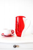 White and red ceramic flagon on white background. White and red ceramic flagon on white wall background Stock Photo