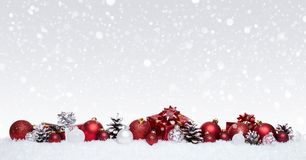 White and red christmas balls with xmas presents in a row isolated on snow royalty free stock image