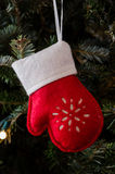 White and Red Felt Mitten Ornament Vertical. A felt red and white mitten ornament hangs from a gently lit Christmas tree stock images