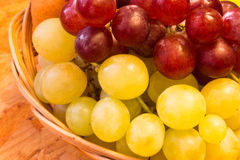 White and red grapes in wickerwork basket. On a wooden board Royalty Free Stock Image