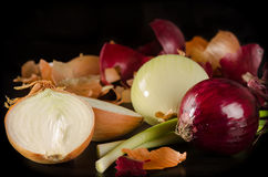 White, red and green onion with the husk on black wooden backgro Royalty Free Stock Photo