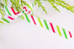 White, red and green striped silk ribbon tied in a bow on a whit Stock Photo