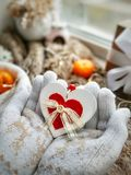 Love holiday greeting card. White and red heart on hands in knitted mittens. stock photo
