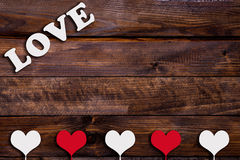 White and red heart with the word Love. On a stick on a wooden background Royalty Free Stock Photos
