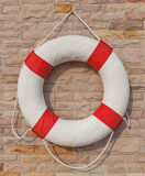 The white and red life buoy hanging on the brick wall around the Stock Images