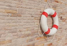 The white and red life buoy is hanging on the brick wall around Stock Image