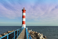 White and red lighthouse at the end of the pier Stock Photos