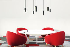 White and red office waiting room or a staff room. Office waiting room or a staff room interior with a round table, red comfortable armchairs standing near it, a Stock Photo