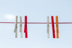 White, Red, Orange Cloth Pins Hanging on Red Rope. Over blue sky Royalty Free Stock Photo