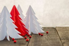 White  and red origami Christmas tree with red decoration. White and red origami Christmas tree with red decorations on a wooden table and a white background Stock Photography