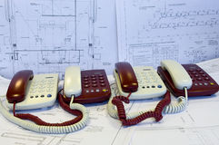 White and red phones are on the working drawings. White and red phones are on the surface covered by working drawings (papers). Working place Royalty Free Stock Photography