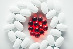 White and red pills. Top view of white capsules and red pills on grey Stock Photography
