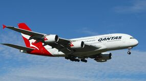 White and Red Qantas Airplane Fly High Under Blue and White Clouds Stock Photography