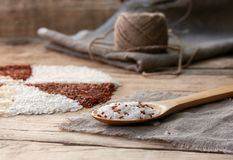 White and red rice in a wooden spoon. On the sackcloth with ball of twine on an old wooden table Stock Images
