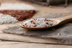 White and red rice in a wooden spoon. On the sackcloth with ball of twine on an old wooden table Royalty Free Stock Photography