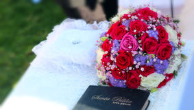 Bible and a White and red roses wedding bouquet. A big bouquet of roses over a table in a wedding ceremony next to a bible Stock Images