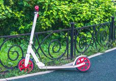 White and red scooter leaned on fence in park stock photos