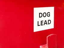 A white and red sign saying dog lead on a red bin box for litter. Clean nature environment animals Royalty Free Stock Photos