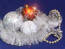 White, red and silver glass New Year`s balls, brilliant tinsel, cones and a pearl beads on a blue background - New Year`s composit. Ion, a card Stock Image