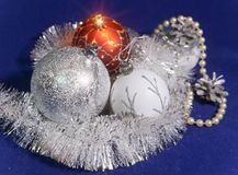 White, red and silver glass New Year`s balls, brilliant tinsel, cones and a pearl beads on a blue background - New Year`s composit. Ion, a card Royalty Free Stock Images