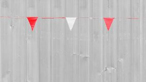 White and red triangle flag is hanging. Front the metal wall royalty free stock photography