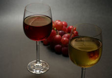 White and red wine. With grapes on dark background, narrow focus Stock Image