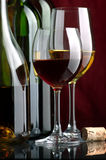 White and red wine. Bottles and glasses of excellent wine on a dark background Stock Images