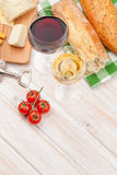White and red wine, cheese and bread on white wooden table backg Stock Images