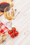 White and red wine, cheese and bread on white wooden table backg Royalty Free Stock Photography